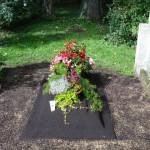 Provisorisches Grab mit Kränzen und Blumenschmuck